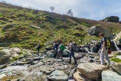 Groep wandelaars die de Alpen, openluchtactiviteiten in de zomer onderzoeken Stock Foto's