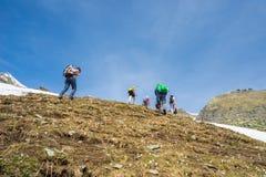 Groep wandelaars die de Alpen, openluchtactiviteiten in de zomer onderzoeken Stock Fotografie