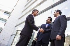 Groep zakenlieden die handen buiten bureau schudden Royalty-vrije Stock Foto