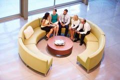 Groep Zakenlui die Vergadering in Bureauhal hebben Royalty-vrije Stock Foto's