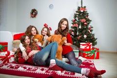 Groep zeer jonge vrouwenbespreking over giften binnen Stock Afbeelding