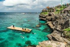 Groeps Chinese toeristen die in turkooise overzees over rotsachtige kust van het Crystal Cove-eiland dichtbij Boracay snorkelen stock afbeeldingen