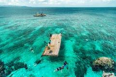 Groeps Chinese toeristen die in turkooise overzees over rotsachtige kust van het Crystal Cove-eiland dichtbij Boracay snorkelen stock foto