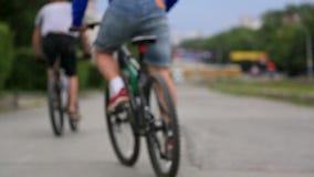 Groepsmensen die fiets in park berijden Achter mening Fitness, sport, mensen en gezond concept Onherkenbare beroeps stock footage
