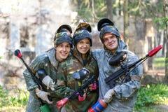 Groepsportret van drie glimlachende paintball spelers in openlucht stock afbeeldingen