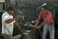 Groepsportret van smeden aan het werk in smidse stock afbeeldingen