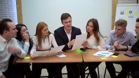 Groepswerk, collectieve en mensenconcept - commercieel team met documenten, vergadering en het bespreken van project op kantoor 4 stock footage
