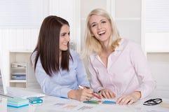 Groepswerk op kantoor met twee jonge aantrekkelijke onderneemsters. Royalty-vrije Stock Afbeelding