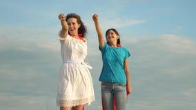 Groepswerk superheroes twee meisjes in rode mantels van superheroestribune tegen een blauwe hemel, de wind blaast een mantel op m stock videobeelden