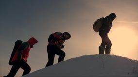 Groepswerk van bedrijfsmensen drie klimmers beklimmen achter elkaar op een snow-covered heuvel het team van bedrijfsmensen gaat stock footage
