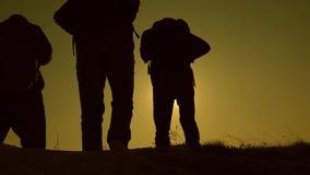 Groepswerk van bedrijfsmensen Drie reizigers dalen van heuvel in stralen van zon nadat andere voorbij horizon gaat langzaam stock videobeelden