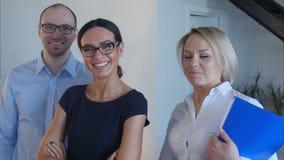 Groepswerk van jongeren op het kantoor die aan de camera en het glimlachen kijken stock footage