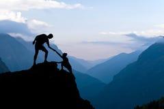 Groepswerkpaar die helpend hand beklimmen Royalty-vrije Stock Fotografie