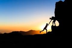 Groepswerkpaar die helpend hand beklimmen Stock Foto