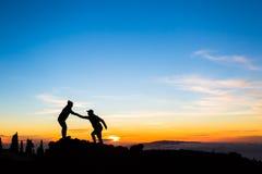Groepswerkpaar die helpend hand beklimmen stock afbeelding