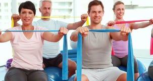 Groepszitting die op oefeningsballen weerstandsbanden uitrekken stock videobeelden