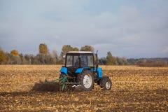 Großer blauer Traktorpflug pflog Land, nachdem er die Maisernte auf einem sonnigen geerntet hatte, klar, Herbsttag Lizenzfreie Stockfotografie