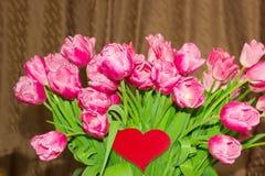 Großer Blumenstrauß von den Tulpen und von Herzen gemacht vom roten Papier Stockfotos