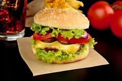 Großer Cheeseburger des Menüs mit Pommes-Frites und Glas Kolabaum auf hölzernem schwarzem Schreibtisch auf Schwarzem Lizenzfreies Stockbild