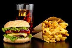 Großer Cheeseburger mit Glas Kolabaum und Pommes-Frites auf schwarzem De Stockbilder
