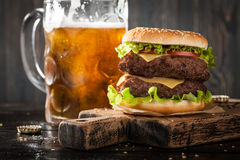 Großer Hamburger und Becher Bier Lizenzfreie Stockfotos