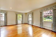 Großer leerer Raum mit Massivholzboden und Vorhängen. Altes Luxushaus. Lizenzfreies Stockfoto