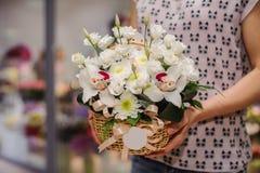 Großer weißer Blumenstrauß mit enormen Orchideen in den Händen Stockfotos