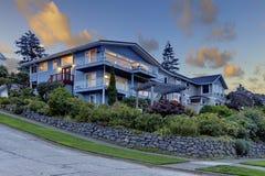 Großes dreistöckiges hohes blaues Haus mit Sommerlandschaft und Felsenwand Stockfotografie