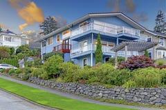 Großes dreistöckiges hohes blaues Haus mit Sommerlandschaft und Felsenwand Stockbild