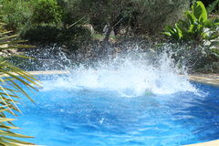 Großes Wasserspritzen im Pool Stockfotos