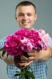Groeten Sluit omhoog van de glimlachende mens die boeket van bloemen geven stock fotografie