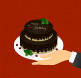 Groetkaart met het beeld van chocoladecake op twee niveaus met de woorden Gelukkige Verjaardag en kersen in een hand Stock Foto