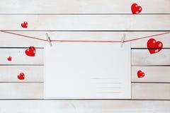 Groetkaart met ruimte voor tekst het hangen op een rode draad over een witte houten achtergrond stock foto's