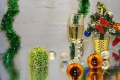 Groetkaart van Kerstmis en taxushout de ballen van de jaardecoratie, klatergoud, kaars en twee glazen champagne met bezinning, ex stock fotografie