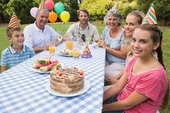 Großfamilie, die draußen Geburtstag der kleinen Mädchen am Picknicktisch feiert Stockfotografie