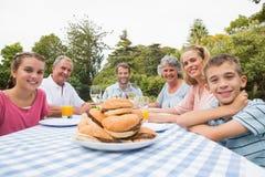 Großfamilie, die draußen am Picknicktisch isst Stockfotografie
