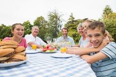 Großfamilie, die draußen am Picknicktisch zu Abend isst Stockbild