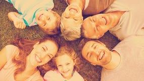 Großfamilie, die im Kreis am Park liegt Stockfotografie