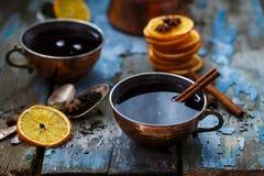 Grog in koperkoppen met kruiden en oranje plakken stock foto's