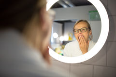 Groggy, young woman yawning in front of her bathroom mirror Stock Photography