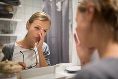 Grogue, jovem mulher que boceja na frente de seu espelho do banheiro fotos de stock