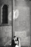 Grom huging kissing bride with red hair near wall outdoors Lviv.  royalty free stock photography
