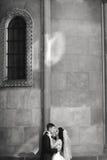 Grom som utomhus huging den kyssande bruden med rött hår nära väggen Lviv Royaltyfri Fotografi