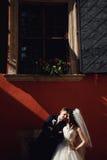 Grom som utomhus huging den kyssande bruden med rött hår nära väggen Lviv Arkivfoto