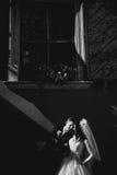 Grom som utomhus huging den kyssande bruden med rött hår nära väggen Lviv Royaltyfria Foton