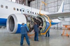 Gromadzić, zamienia parowozowe części samolot po naprawy Specjalisty mechanik kontroluje żurawia samolot Pojęcia maint Fotografia Royalty Free
