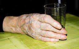 Großmutter, die ein Glas Wasser hält Stockbild