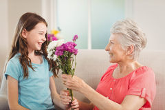 Großmutter, die ihrer Enkelin einen Blumenstrauß gibt Lizenzfreies Stockfoto
