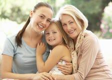 Großmutter mit der Tochter und Enkelin, die zusammen auf Sofa lachen Stockbild