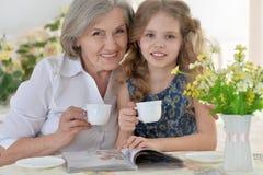Großmutter mit trinkendem Tee des kleinen Mädchens Lizenzfreies Stockfoto